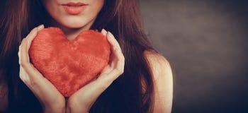 La femme tient le symbole rouge d'amour de coeur Images stock