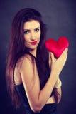 La femme tient le symbole rouge d'amour de coeur Photos libres de droits