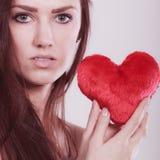 La femme tient le symbole rouge d'amour de coeur Photographie stock libre de droits