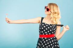 La femme tient le symbole rouge d'amour de coeur et la sucrerie de lucette Photographie stock