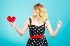La femme tient le symbole rouge d'amour de coeur et la sucrerie de lucette Images libres de droits