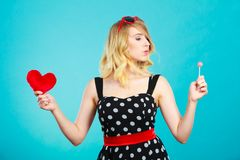 La femme tient le symbole rouge d'amour de coeur et la sucrerie de lucette Photo stock