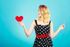 La femme tient le symbole rouge d'amour de coeur et la sucrerie de lucette Images stock