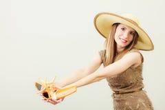 La femme tient les lunettes de soleil et la lotion de protection solaire Images libres de droits