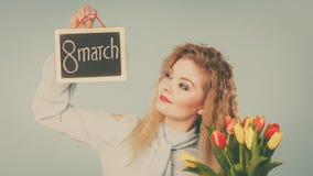 La femme tient les tulipes, conseil avec texte le 8 mars Photographie stock