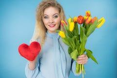 La femme tient les tulipes et le coeur rouge image libre de droits