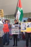 La femme tient un drapeau palestinien et un signe Israël de protestation Photo libre de droits