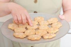 La femme tient un plat avec des biscuits Photo stock