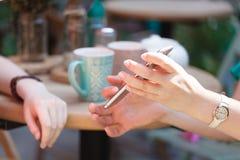 La femme tient un smartphone dans elle remettent une table dans un café, montre à son ami un écran avec une photo Photo stock