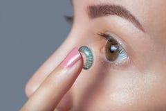 La femme tient un verre de contact bleu sur son doigt Photographie stock libre de droits