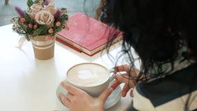 La femme tient une tasse de cappuccino avec un coeur sur le crema banque de vidéos