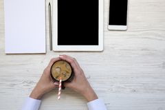 La femme tient une tasse de latte de glace Espace de travail féminin avec le smartpho Images libres de droits