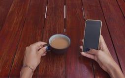 La femme tient une tasse de thé et de smartphone Image libre de droits