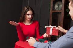 La femme timide refuse le cadeau dans le restaurant Image stock