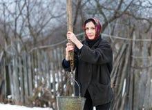 La femme tire l'eau du puits Photographie stock libre de droits