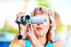 La femme tire la vidéo avec l'intérêt au caméscope Photos stock