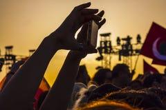 La femme tire la vidéo avec son smartphone dans le coucher du soleil images stock