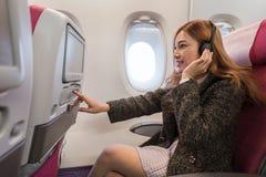 La femme touchant l'?cran de divertissement d'affichage ? cristaux liquides sur l'avion chronom?trent en vol photo stock