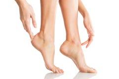 La femme touche tendrement ses pieds Image libre de droits