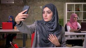 La femme très assez Arabe s'assied au bureau et prend le selfie avec le regard calme sérieux, le hijab et la vue islamique, moder clips vidéos