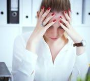 La femme très fatiguée d'affaires prooped son front à la main à côté d'un ordinateur portable Date-butoir ou concept de surmenage photographie stock