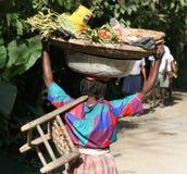La femme transporte des marchandises sur le chef et le corps en le Haïti Photographie stock libre de droits