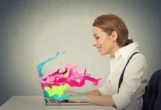 La femme travaillant sur l'ordinateur coloré éclabousse sortir de l'écran Photographie stock