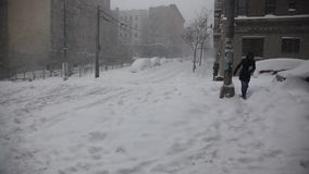 La femme traverse la rue pendant la tempête de neige banque de vidéos