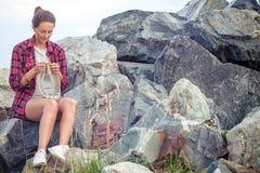 La femme tricote avec des aiguilles de tricotage un chandail gris Images stock