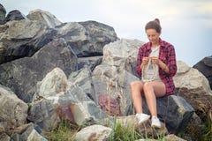La femme tricote avec des aiguilles de tricotage un chandail gris Image libre de droits