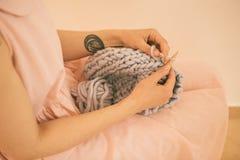 La femme tricote sur le tricotage de tricotage Nuances sensibles roses Image stock