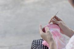 La femme tricote un crochet d'un fil rose et blanc Photo stock