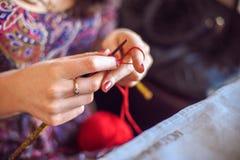 La femme tricote un fil rouge de chandail Image stock