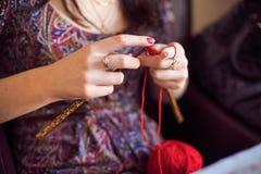 La femme tricote un fil rouge de chandail Photographie stock libre de droits