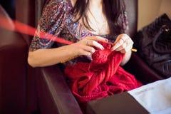 La femme tricote un fil rouge de chandail Photographie stock