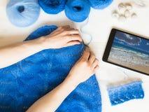 La femme tricote un modèle sur la table Images libres de droits
