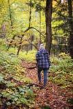 La femme trimardant dans la chute part sur la traînée de forêt image stock