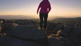 La femme trimardant dans le mont Kosciuszko au coucher du soleil, risquent le mode de vie actif extérieur banque de vidéos