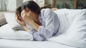 La femme triste est des pyjamas se situe dans le lit et pleure après combat avec son mari de nouveau à qui se trouve près de elle banque de vidéos