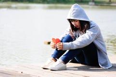 La femme triste et déçue s'assied près de la rivière Image libre de droits