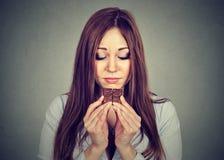 La femme triste a fatigué des restrictions de régime implorant le chocolat Photographie stock