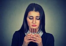 La femme triste a fatigué des restrictions de régime implorant le chocolat de bonbons Image libre de droits