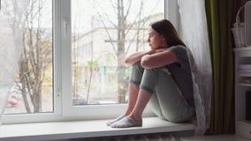 La femme triste s'assied sur le rebord de fenêtre et regarde le jour nuageux d'automne banque de vidéos