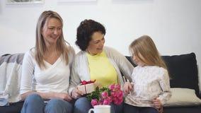 La femme trois s'assied sur le divan et sourit directement à la caméra ensemble banque de vidéos