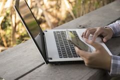 La femme a utilisé l'ordinateur et le téléphone intelligent sur la table en bois images stock