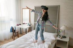 La femme utilisant son dispositif de VR et ouvrent ses bras photographie stock