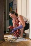 La femme utilise l'arme à feu de chaleur pour ferrailler la peinture sur l'équilibre à la maison Photographie stock