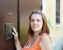 La femme utilise l'intercom Photographie stock libre de droits