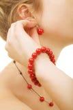 La femme utilise les boucles d'oreille rouges Photographie stock