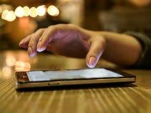 La femme utilise un smartphone le soir tout en se reposant dans un café, fond brouillé images stock